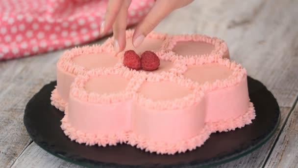 Pekařský šéfkuchař zdobí růžový dort ve tvaru květiny s čerstvými malinami. Řady.