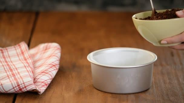 Žena dělá chutný tvarohový koláč v kuchyni. Dělat dort základ sušenek a másla.