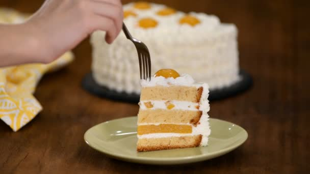 Nő eszik friss torta őszibarack és sajt krém.