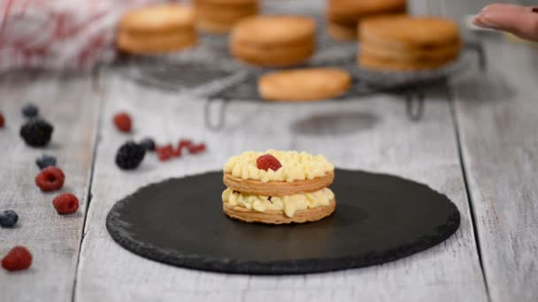 A cukrász francia Mille Feuille-t készít sodóval és bogyókkal. Francia desszert millefeuille puff tészta és tejsodó krém.