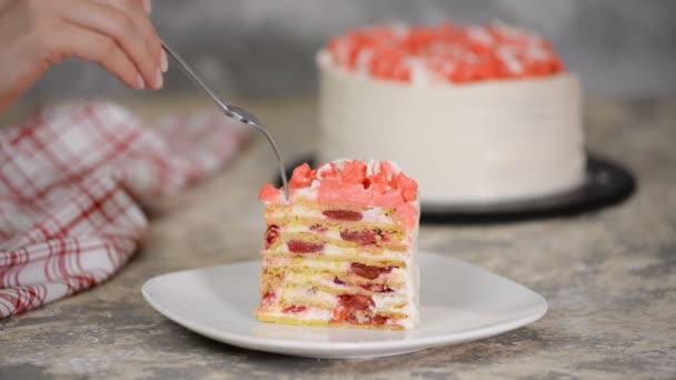 Megenni egy szelet meggyes tortát tejföllel, közelről.