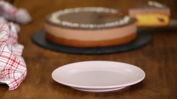 Stück Schokolade Kirsch-Mousse-Kuchen auf einem rosa Teller.
