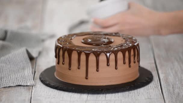 Schokoladenkuchen mit geschmolzener Schokolade glasieren. Frau gießt Schokolade über Kuchen. hausgemachter Kakaokuchen.