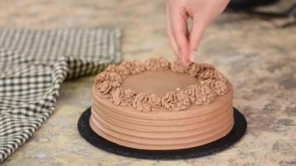Detailní záběr oříšků na smetaně z čokoládového houbového dortu. Pekař zdobené čokoládový dort s ořechem.