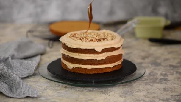 Cukrář nalévá karamel na houbový dort. Výroba dortu v pekárně.