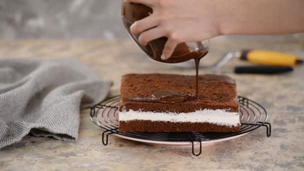 Schokoladenglasur auf Kuchen gießen. Der Konditor glasiert eine Torte.