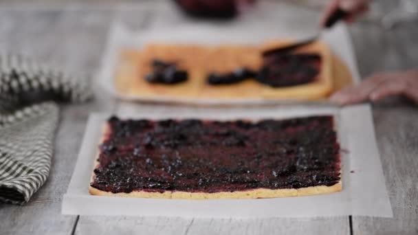 Dívka pomazáním džem na plochém listu dortu, aby se dort se svislými vrstvami doma.