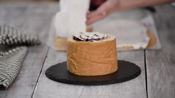 Pastry chef making sponge cake with vertical layers and blackcurrant jam. Series.