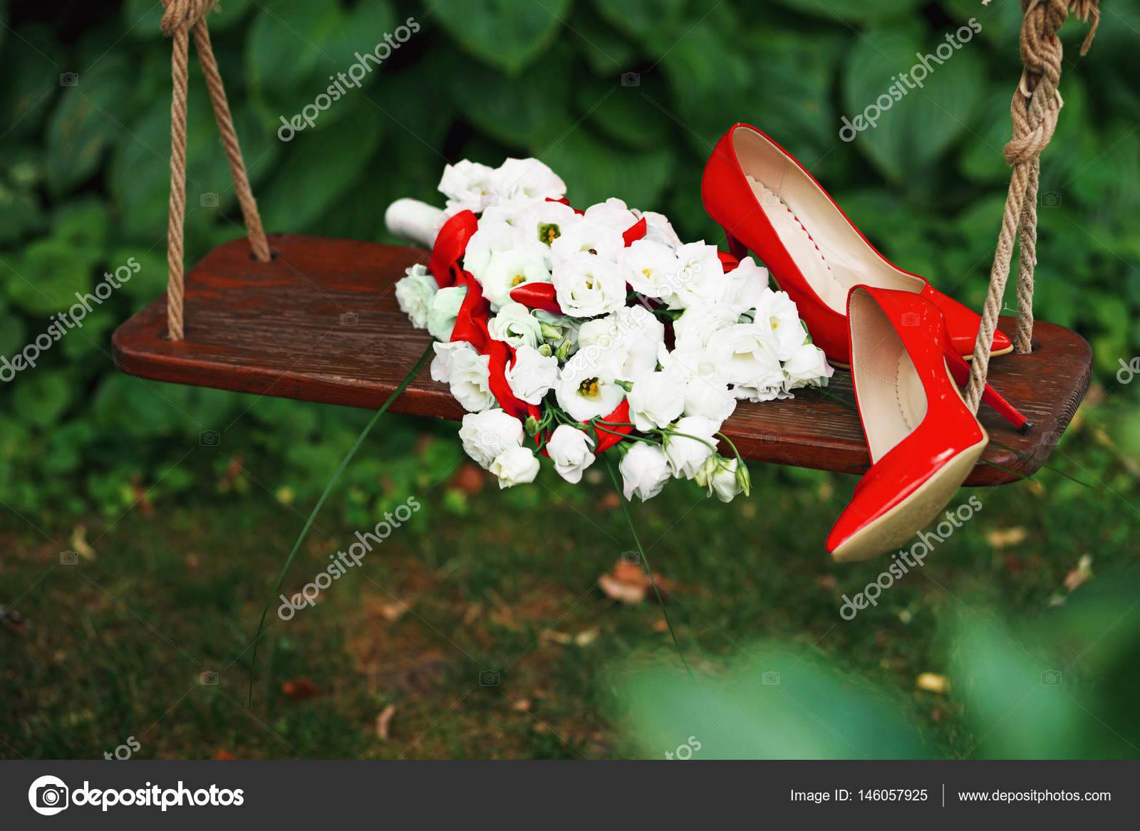 wedding bouquet of white roses and red ribbons and red patent le