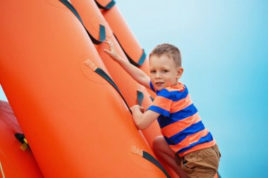 boy playing on an inflatable playground on the beach on a summer