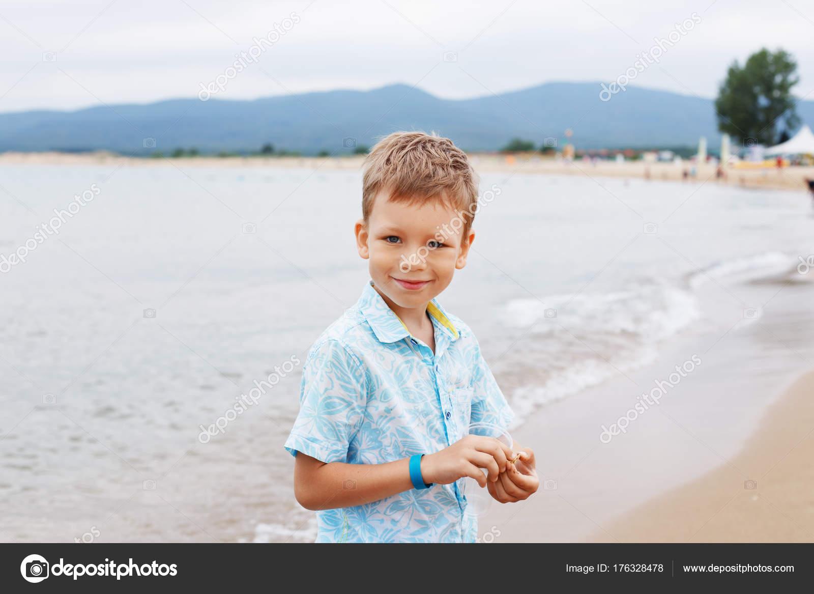 59e01d32a Little boy in shirt and shorts on the beach sand. Little boy hav — Stock