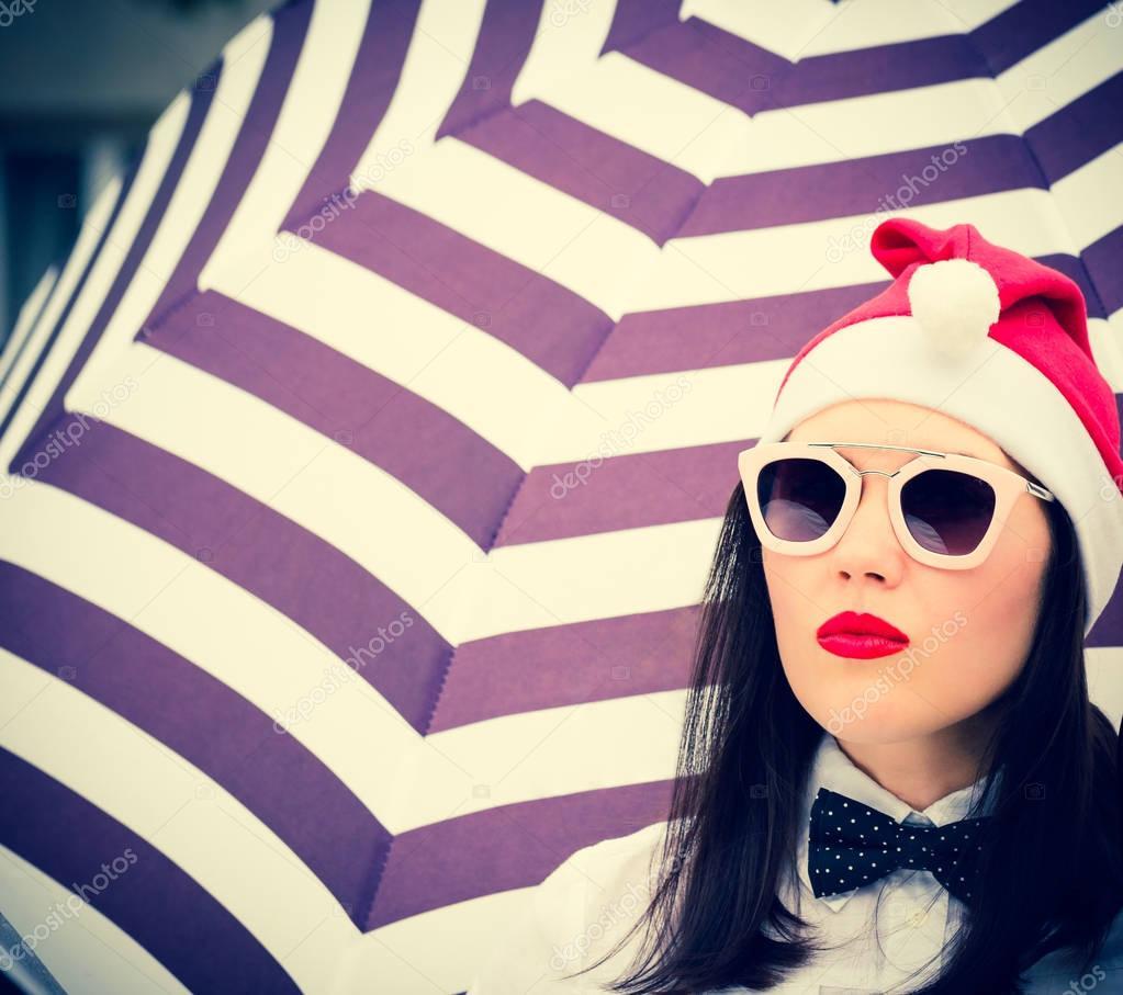 1da1394191c958 Ritratto di una bella ragazza in occhiali da sole con brillante labbra  dipinte accanto a priorità bassa a strisce e cappello di Babbo Natale —  Foto di ...