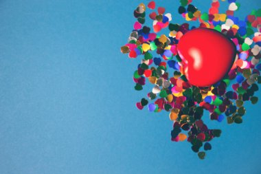 Decorative red heart with colorful confetti on blue background.