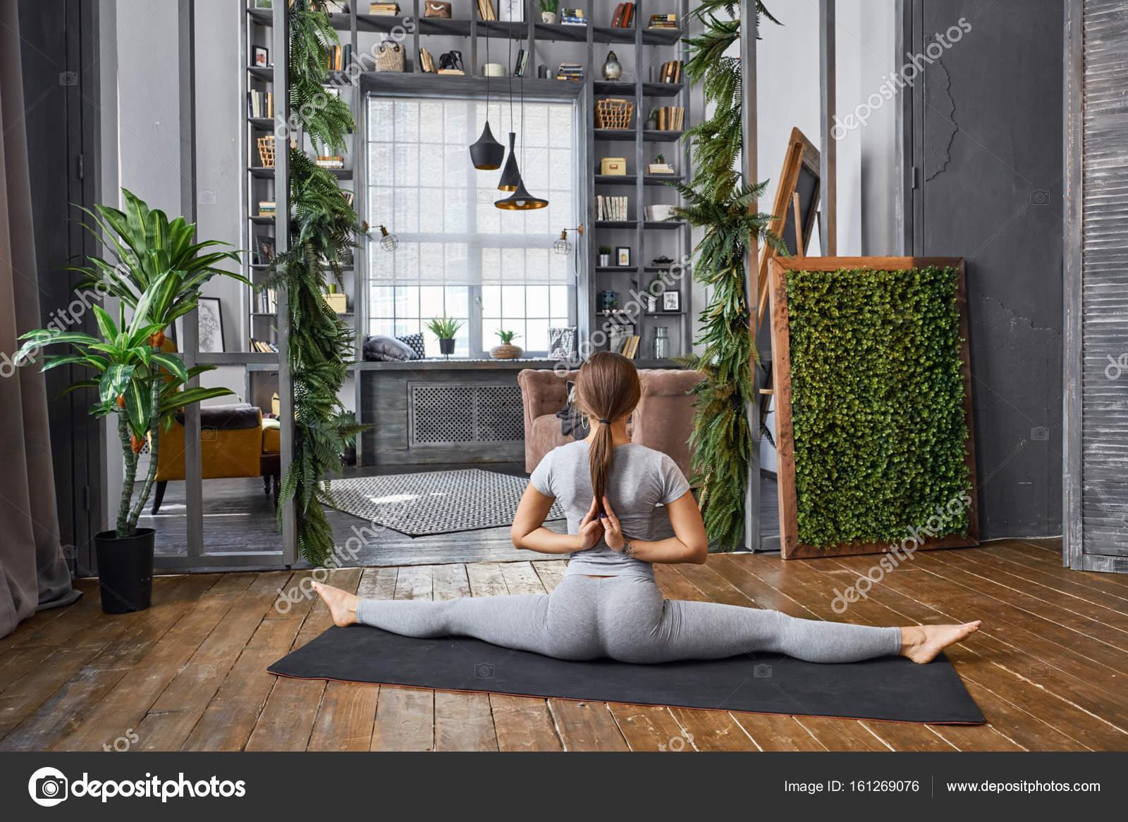 Vrouw beoefenen geavanceerde yoga in de woonkamer u stockfoto