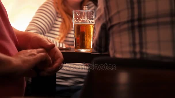 men and women drink beer at a table in a bar