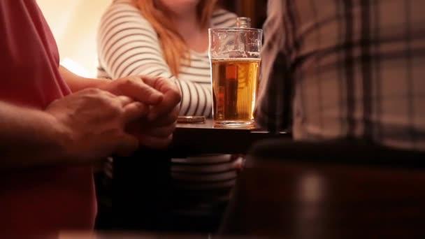 uomini e donne bevono birra al tavolo di un bar
