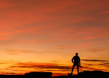 A man standing on top of a building as the sun sets.with camera and take the pictures