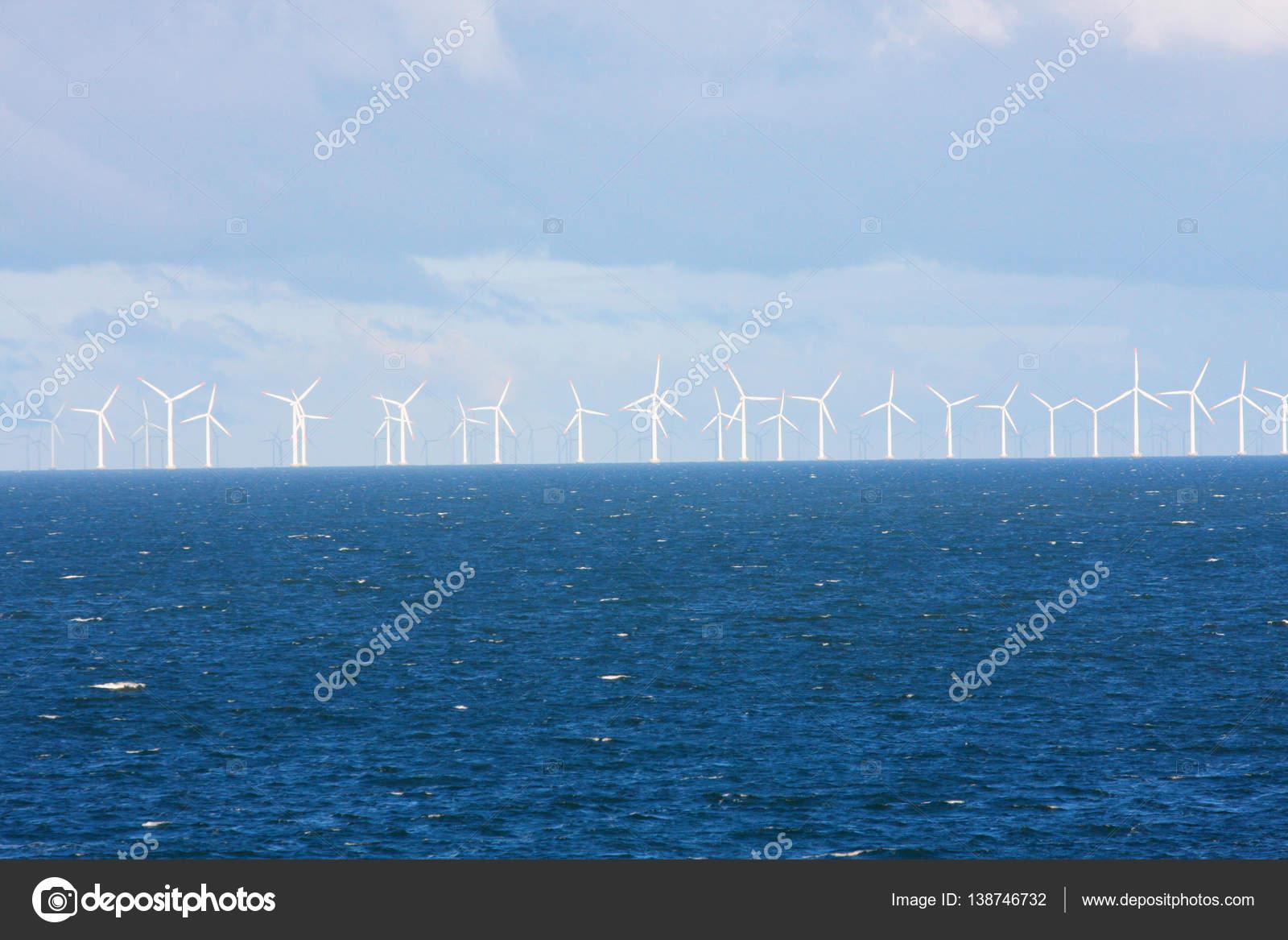 Perspective line of ocean wind mills with dark water and sky — Stock