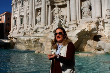Throwing a coin in famous Trevi Fountain in Rome, Italy.