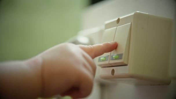 Babys Hand spielt mit elektrischem Lichtschalter