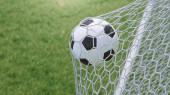 Fotografie Der Ball flog ins Tor. Fußball biegt das Netz, vor dem Hintergrund des Rasens. Fußball im Tornetz auf Rasen Hintergrund. ein Moment der Freude