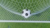 Der Ball flog ins Tor. Fußball biegt das Netz, vor dem Hintergrund des Rasens. Fußball im Tornetz auf Rasen Hintergrund. ein Moment der Freude