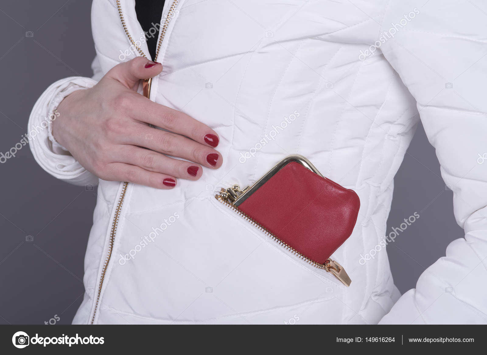 f4067dcf63d4 Woman wearing a white padded jacket with a red purse in the zipped pocket —  Photo by ...
