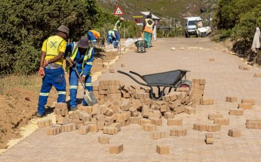 Rooiels, Western Cape, South Africa. December 2019. Workers laying a brick road in the small hamlet of Rooiels.