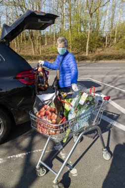 Southampton, England, UK. March 2020. An elderly woman wearing a face mask and rubber gloves for protection during the Coronavirus epidemic loading her grocery shopping into a car.