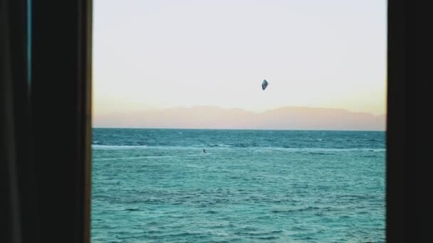 People Kite surfing in beautiful clear water in Dahab Egypt point of view from window. Exploring the blue sea with mountains in the background and people kite surfing, slow motion, 4k