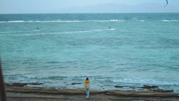 Hübsche Frau beim Gehen und Fotografieren am steinigen Strand in der Nähe des Meeres, die Wellen brechen am Ufer, Ägypten Sinai im Hintergrund, Zeitlupe, 4k