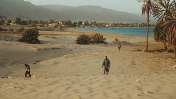 Barátok séta a strandon naplementekor, tenger a háttérben, lassított felvétel.