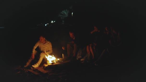 Skupina přátel baví v blízkosti táboráku na pláži u moře v noci, rychlé video, zpomalení, full hd