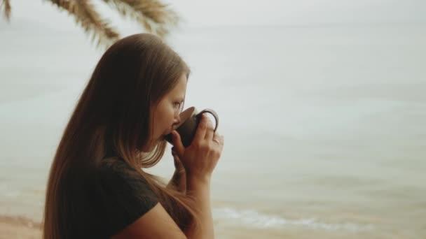 Sama žena pije kávu nebo čaj v dopoledních hodinách na balkóně s modrým výhledem na moře, pohled z okna, rychlé video, zpomalení, full hd
