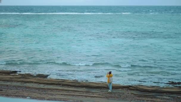 Hübsche Frau zu Fuß und Fotografieren am steinigen Strand am Meer, die Wellen brechen am Ufer, Ägypten Sinai Berg im Hintergrund, Zeitlupe, voll hd