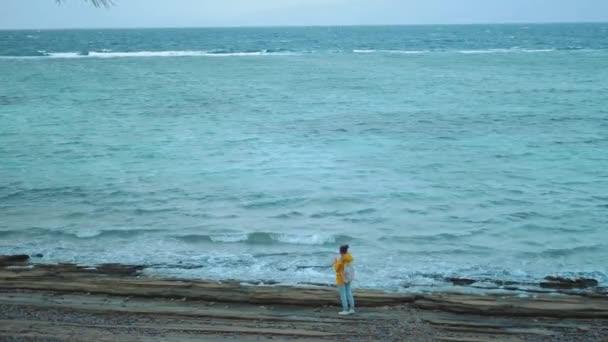 Hübsche Frau beim Wandern und Fotografieren am steinigen Strand in der Nähe des Meeres, die Wellen brechen am Ufer, Ägypten Sinai im Hintergrund, 4k