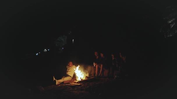 Skupina přátel baví v blízkosti táboráku na pláži u moře v noci, 4k