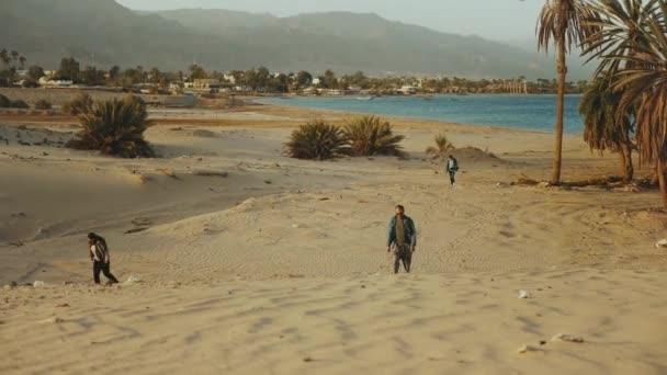 Barátok séta a strandon naplementekor, tenger a háttérben, 4k