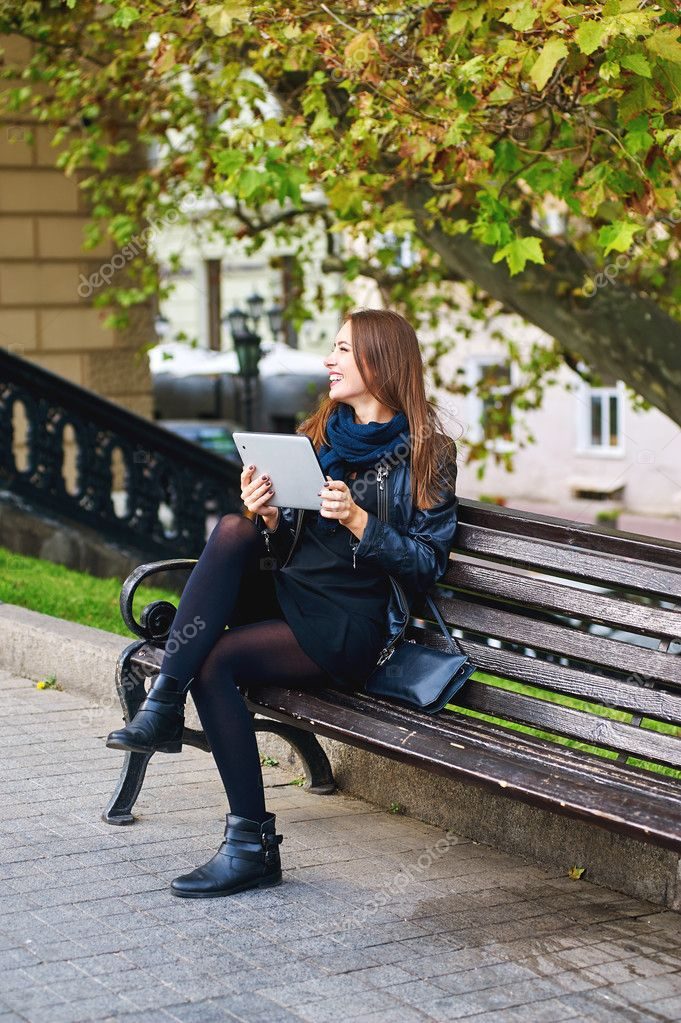 Fun girl communicates through tablet sitting in a city Park