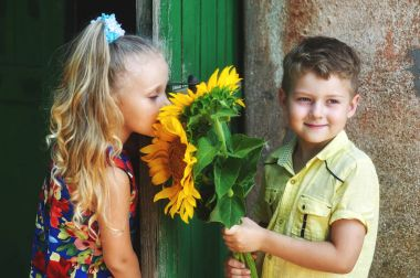 children's friendship and love . Boy with flowers sunflower for girls