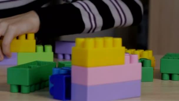 chlapec hrající v barevných bloků, sedící u stolu