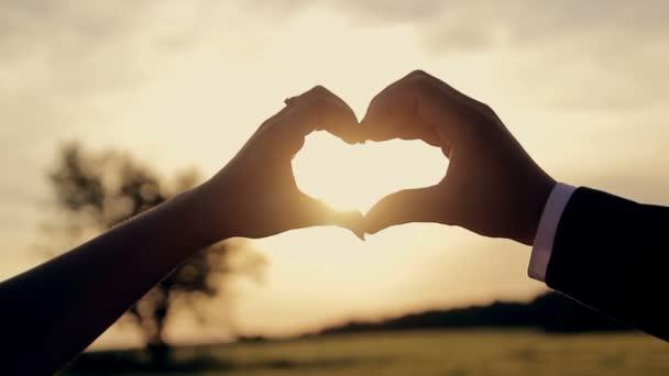 Rukou mužů a žen v podobě srdce na západ slunce