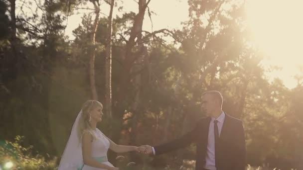 Šťastný ženich drží v náručí a líbá nevěstu