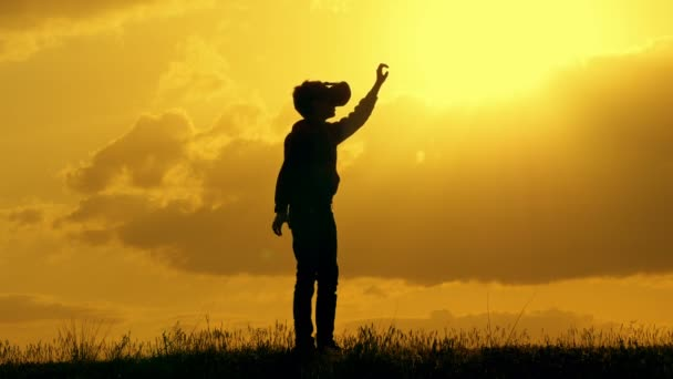 Portrait of boy with outstretched arms using vr glasses in park at sunset.Bokeh