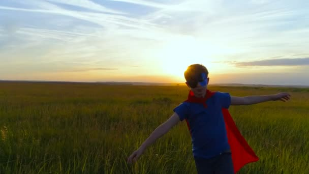 Egy fiú, egy superman jelmez fut a zöld mezőn a naplemente