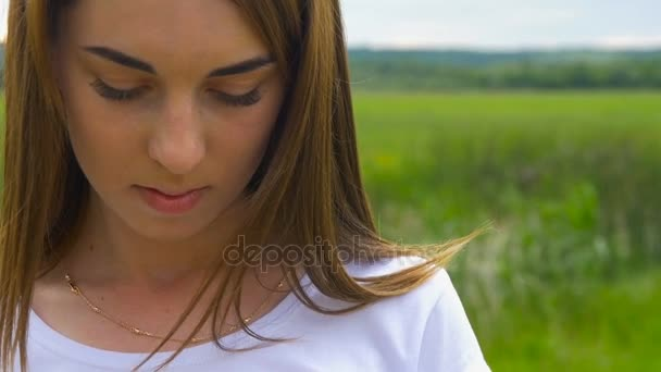 Beautiful young brunette girl outdoors looking at camera.