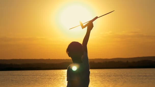 Happy child on a background of an orange sky and lake in summer at sunset, playing with a toy airplane.