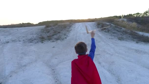 Egy fiú öltözött fel, egy hegyi nézi a naplementét a Superman köpeny állandó