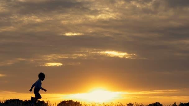 Sagome di bambini correnti in un campo al tramonto