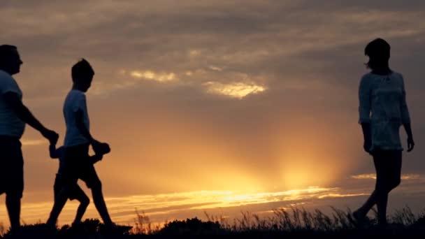 silueta šťastná rodina otec matku a dva syny hrát venku v poli při západu slunce
